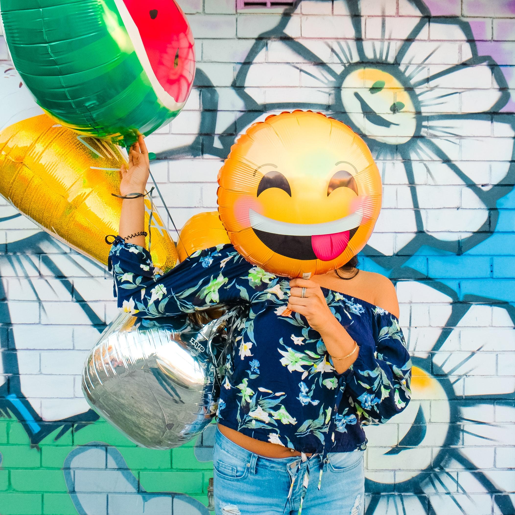 Woman holding up emoji balloon